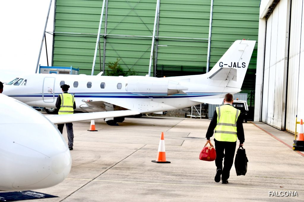 FBO STAFF HELPING CARRYING PASSENGERS LUGGAGE TO PRIVATE JET