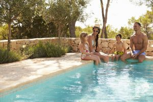 family on vacation relaxing by pool